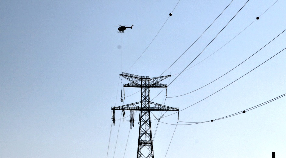 helicopter performing work on transmission line